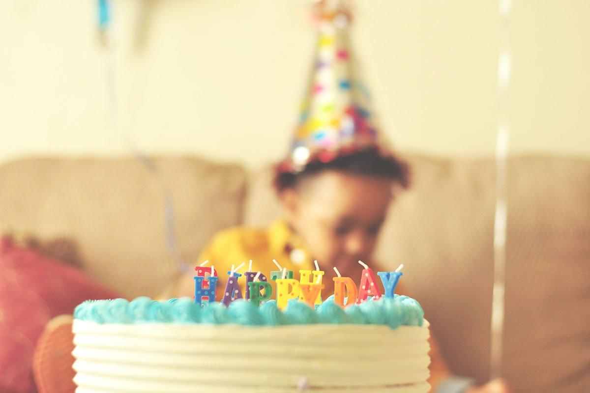 little boy in birthday hat near his birthday cake