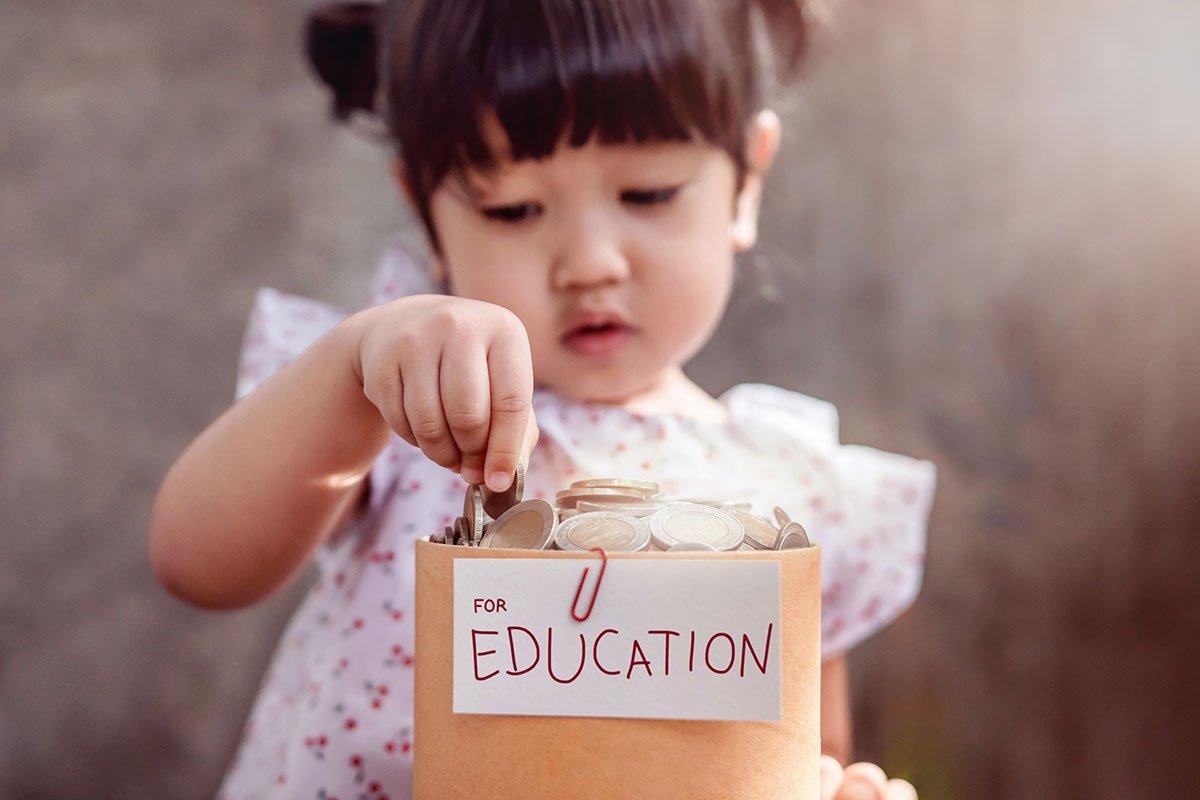 little girl putting money in education savings